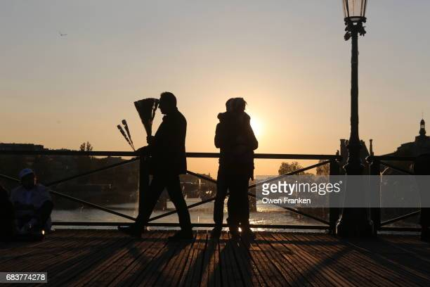 man trying to sell flowers on the Pont des Arts, a footbridge in Paris