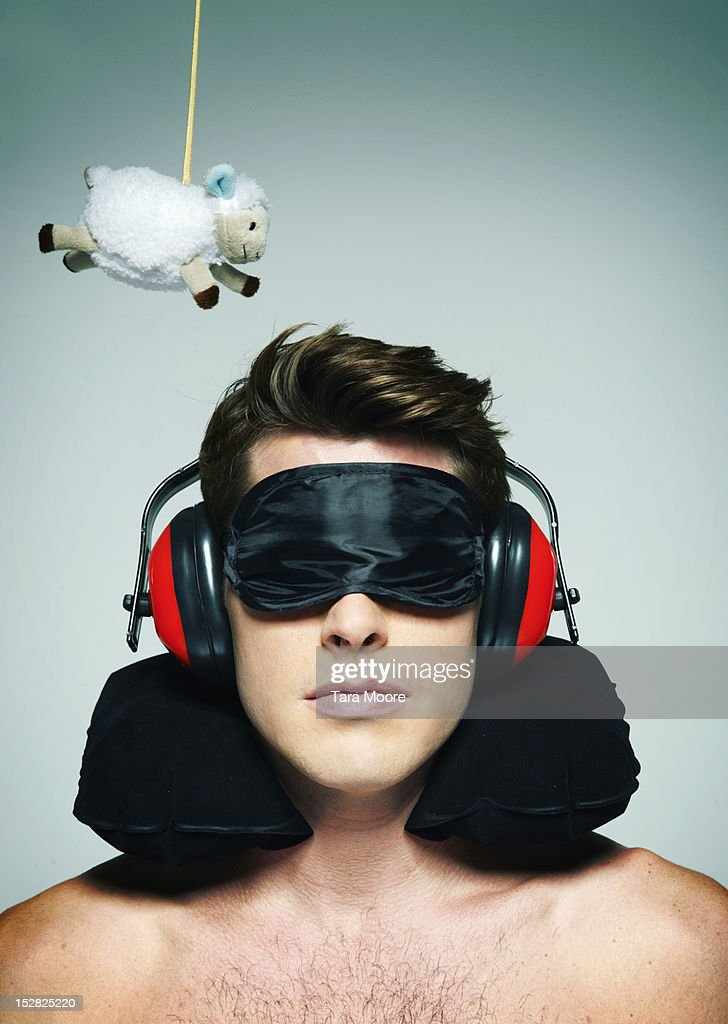man trying to sleep with sheep and sleeping mask : Stock Photo