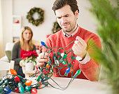 Man trying to untangle Christmas lights