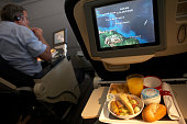 A man tucks in to his inflight meal onboard an Air France Boeing 777 flight from Paris Orly to Cayenne French Guiana Putting more food into his mouth...
