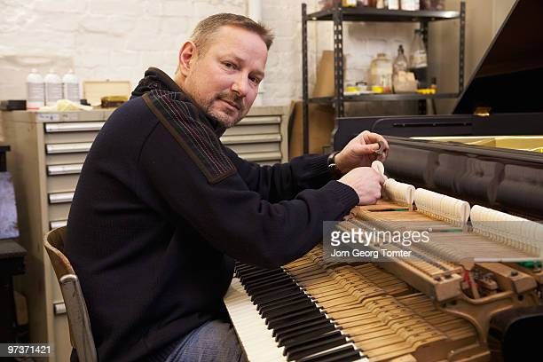 Man tuning a grand piano