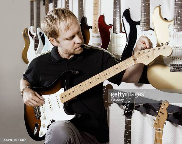 Man tuning electric guitar in music shop, plectrum in mouth