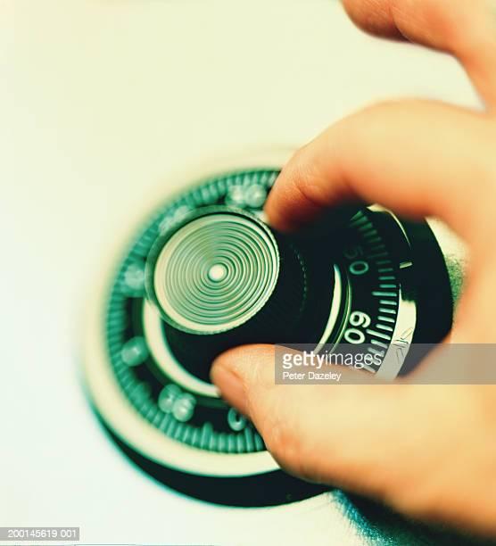 Man turning combination lock, close up