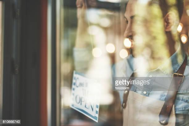 Mann, die Tür-Coffee-Shop Eröffnung Zeichen einschalten