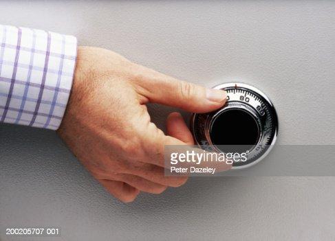 Man turning safe dial, close-up