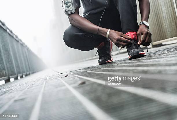 Man tying a shoe before jogging