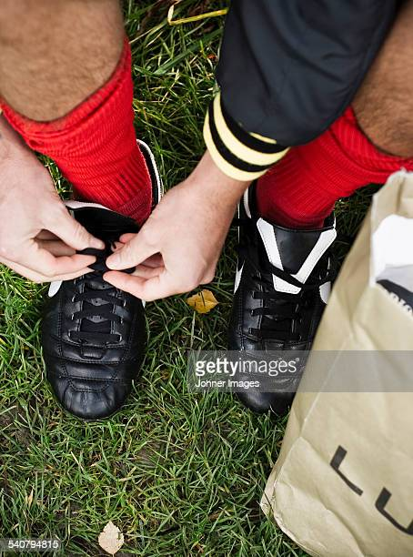 Man tying football shoes