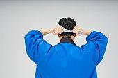Man tying headband, rear view