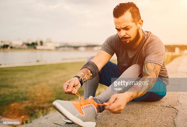 Man tying his sports shoe laces.