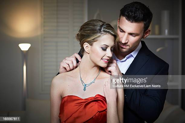 Man tying necklace on girlfriend