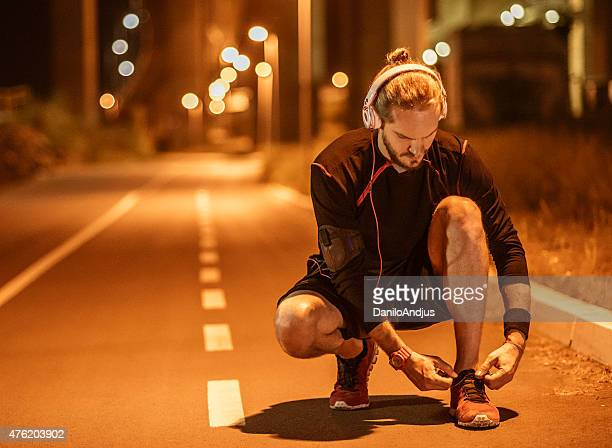 man tying shoe laces and taking a break from jogging