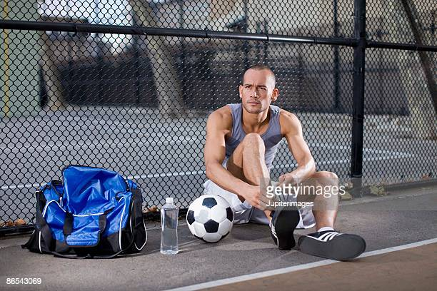 Man tying soccer shoes outdoors