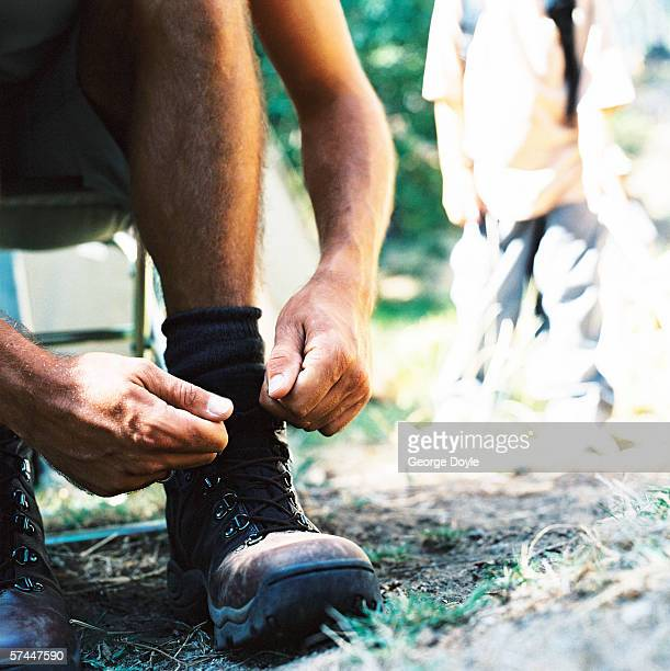 man tying the laces of his boots