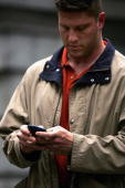 A man types on his Blackberry handheld device April 27 2005 in New York City According to the American Society of Hand Therapists hand held...