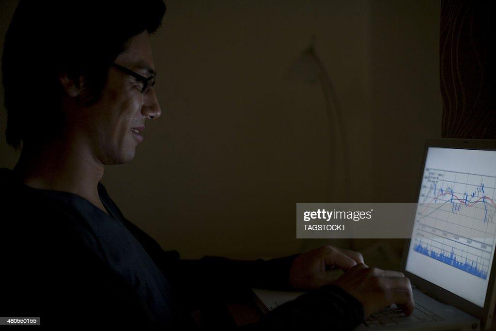 Man typing keyboard of PC in dark room : Stock Photo