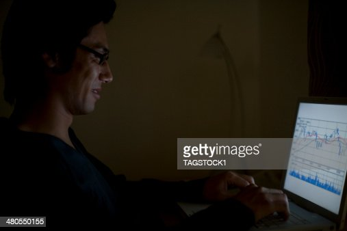 Man typing keyboard of PC in dark room : Stock Photo
