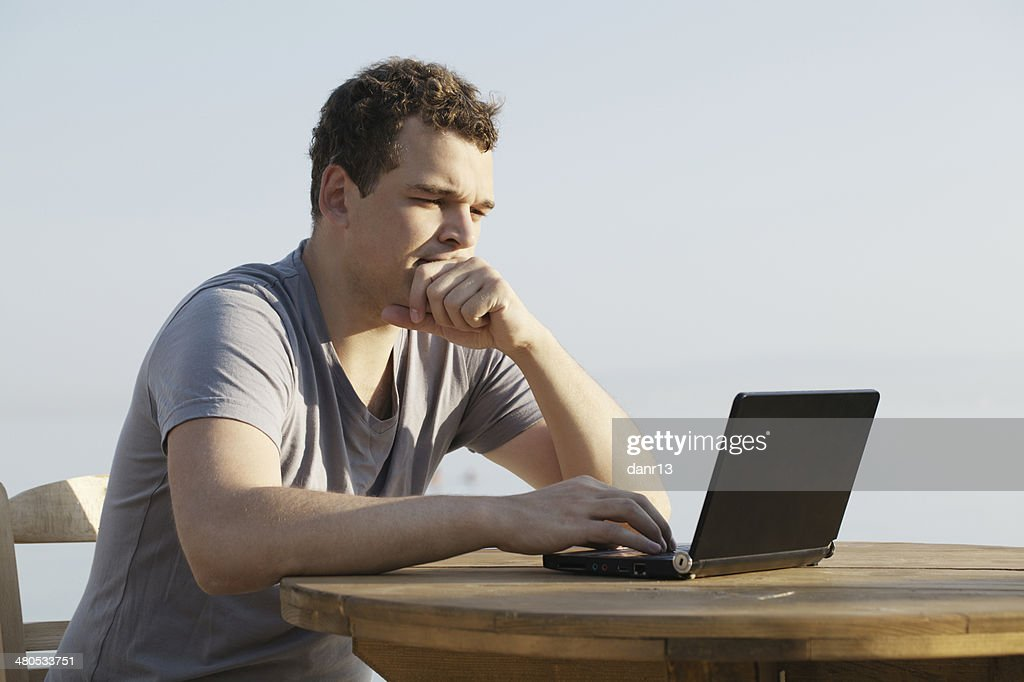 Man typing on a small laptop computer : Stock Photo