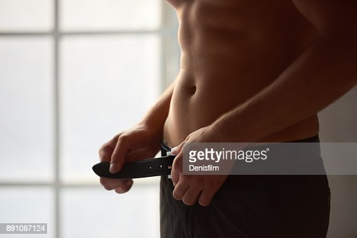 Man unbuckling belt. : Stock Photo