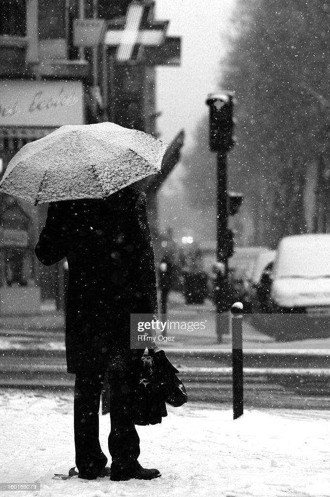 CONTENT] Man under an umbrella in a Paris Avenue. It's snowing.