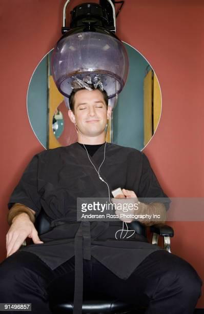 Man under hair dryer in salon