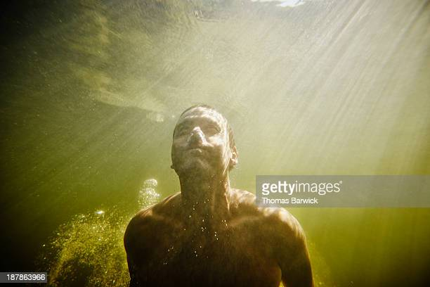 Man underwater swimming towards surface of water