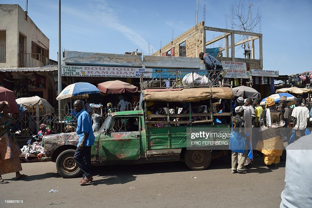 A man unload a Peugeot 404 pick-up used as a taxi on January 21, 2013 in a street of Bamako. AFP/PHOTO ERIC FEFERBERG