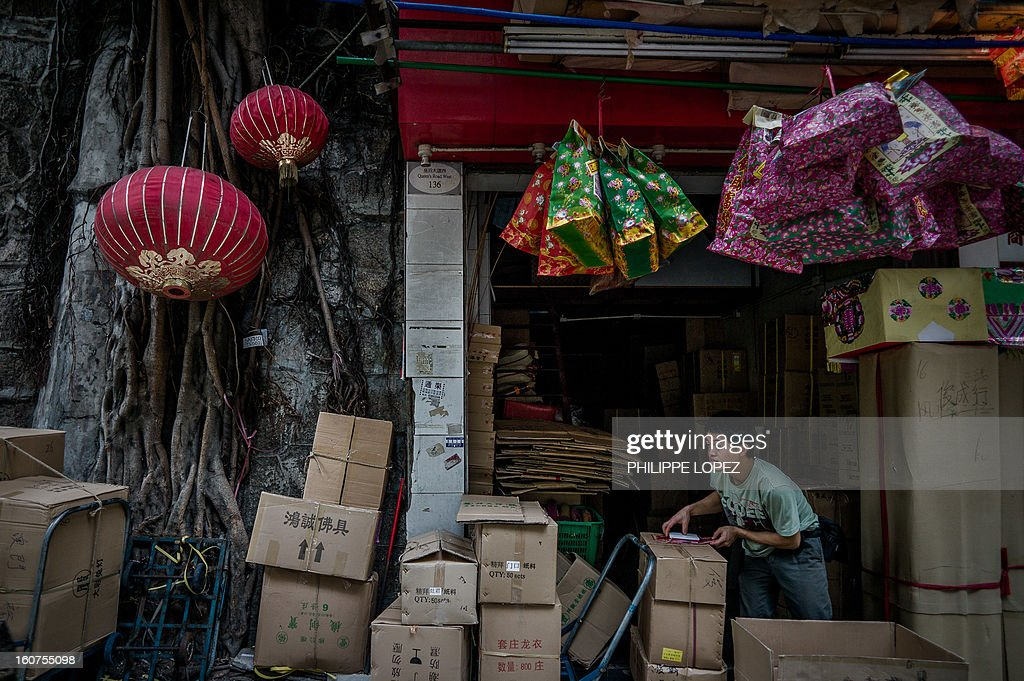 A man unload goods next to lanterns displayed outside a shop for Chinese New Year in Hong Kong on February 5, 2013. The Chinese New Year festival falls on February 10, 2013. AFP PHOTO / Philippe Lopez