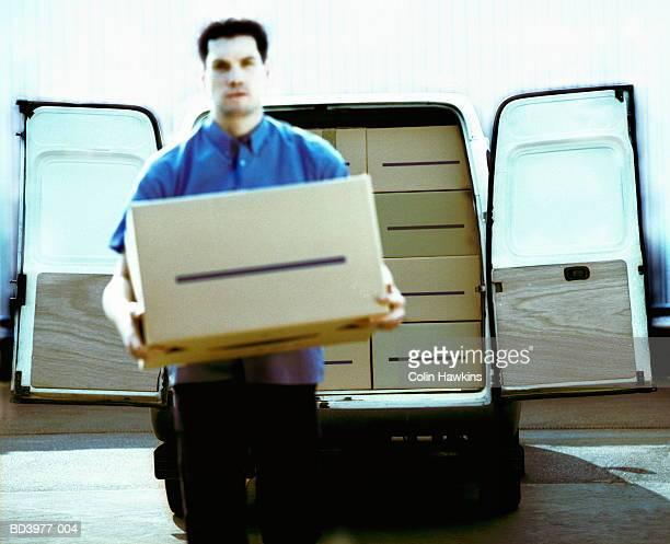 Man unloading box from back of van