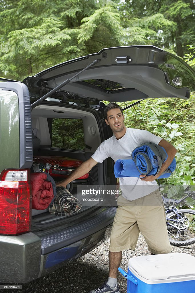 Man unloading car in countryside