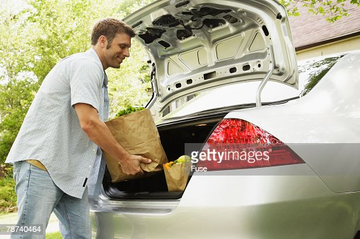 Man Unloading Groceries From Car Trunk