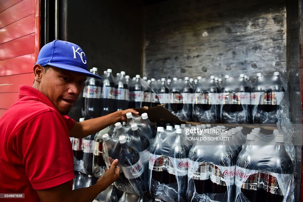 A man unloads bottles of Coca Cola from a truck in Caracas on May 27, 2016. Coca Cola suspended much of its distribution in Venezuela due to a shortage of sugar. / AFP / RONALDO