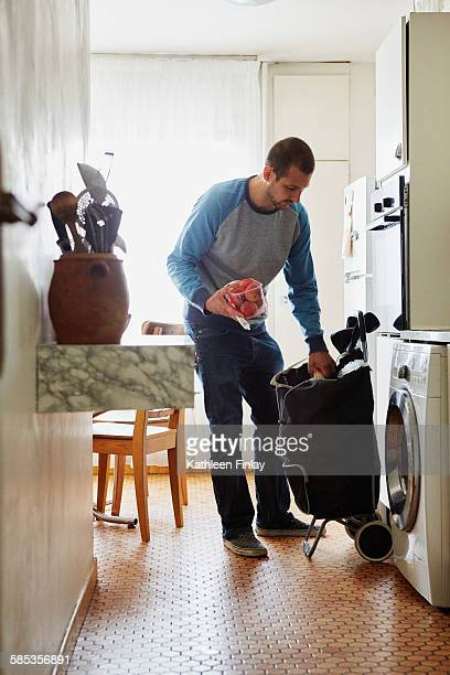 Man unpacking groceries at home