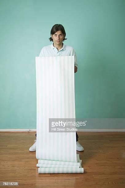 Man Unrolling Long Roll of Striped Wallpaper