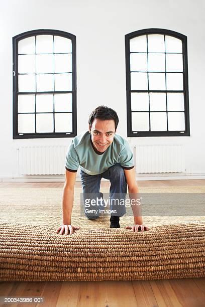 Man unrolling mat on floor, smiling, portrait