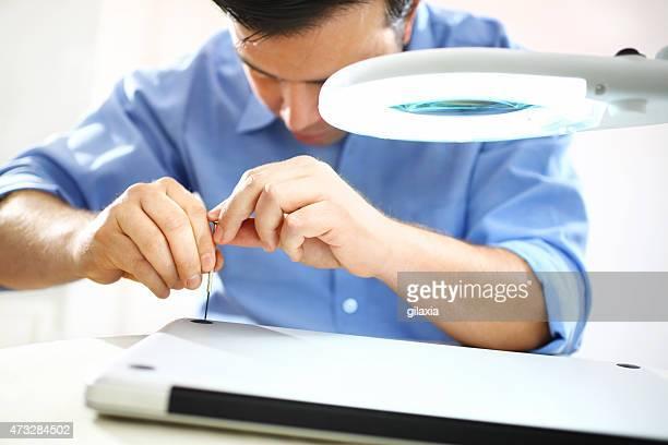 Man unscrewing bottom case of a laptop.