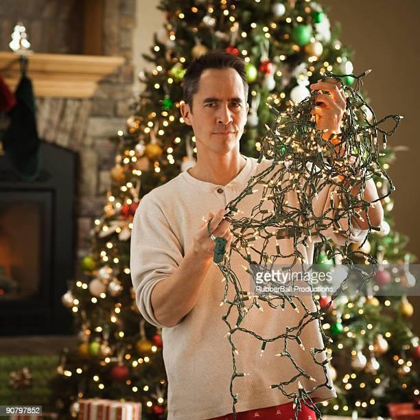 man untangling christmas tree lights