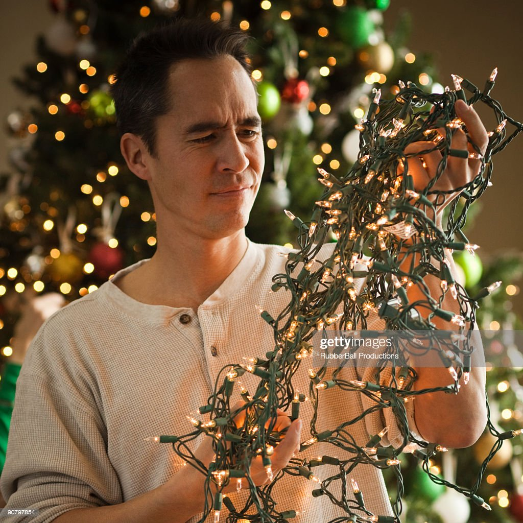 man untangling christmas tree lights : Stock Photo