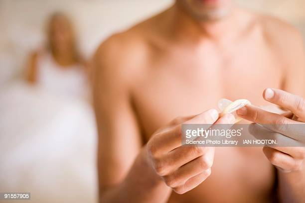 Man unwrapping condom while girlfriend sitting in bed behind him