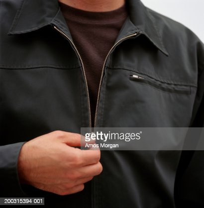 Man unzipping jacket, posing in studio, mid section, close-up