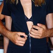 Man unzipping woman's dress