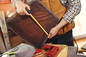 Man upholstering chair in his workshop, measure wooden board