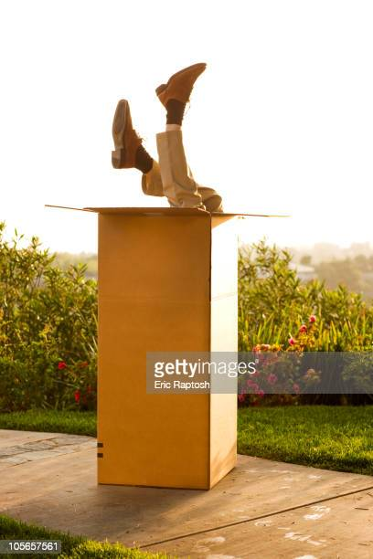 Man upside-down in cardboard box