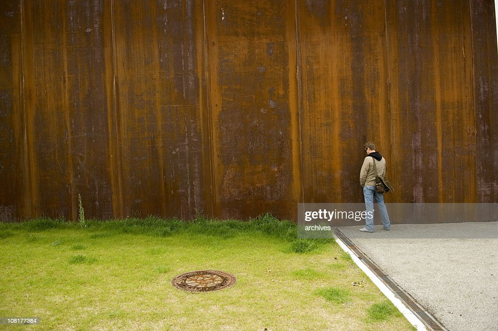 Man Urinating Outside on Rusty Wall Near Green Grass : Stock Photo