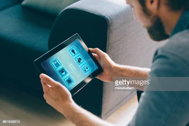 Hombre uso inteligente domótica en sala de estar con tableta digital y aplicaciones móviles