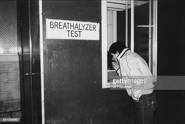 A man uses a breathalyzer test 1983