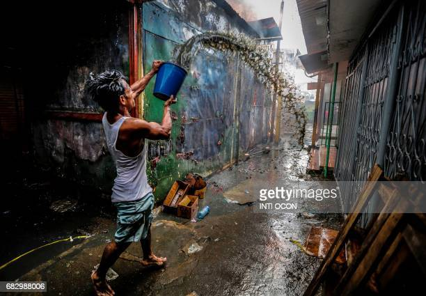 TOPSHOT A man uses a bucket to help put out the fire in the Mercado Oriental where approximately 25 stores have been completely burned in one of the...