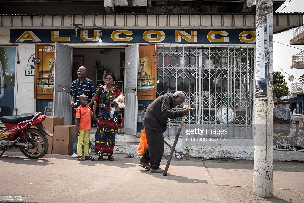 A man uses a cane as he walks past a store in the Poto Poto popular district of the Congolese capital Brazzaville on July 22 2015 AFP PHOTO/FEDERICO...