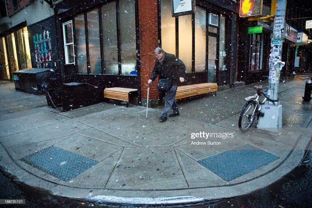 A man uses a cane while walking through a winter snowstorm on December 26, 2012 in New York City. Snow, mixed with and changing to rain, is expected to hit the New York City area this afternoon into the evening.