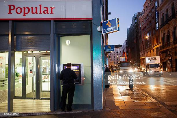 A man uses a cash machine at a Banco Popular branch on September 21 2016 in Madrid Spain Spain's Banco Popular plans to cut around 3000 jobs and...