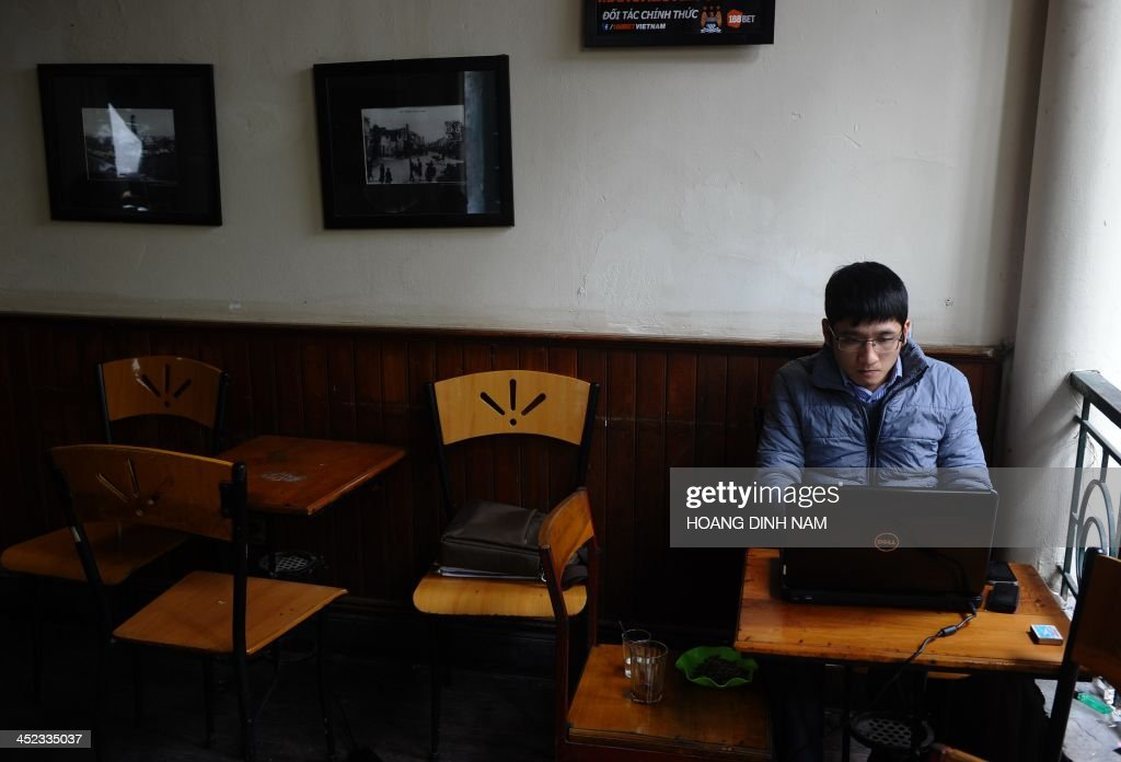 A man uses a computer at a coffee shop in downtown Hanoi on November 28, 2013. Vietnam has intensified a crackdown on online dissent with a new decree that threatens fines of several thousand dollars for anybody criticising the government on Facebook.